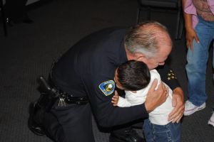 Anaheim Police Chief John Welter gives a hug  at the Kids Creating Change graduation ceremony