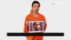 Kenji Goto holds a picture of fellow Japanese captive, Haruna Yukawa.