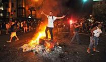 A man stands on top of a burning newspaper stand in San Francisco's Mission district  after the San Francisco Giants beat the Kansas City Royals in the World Series on October 29, 2014.