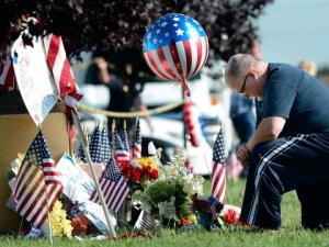 Bill Lettmkuhl by a makeshift memorial near the Armed Forces Career Center on Friday in Chattanooga, Tennessee. -AP Photo by Mark Zaleski